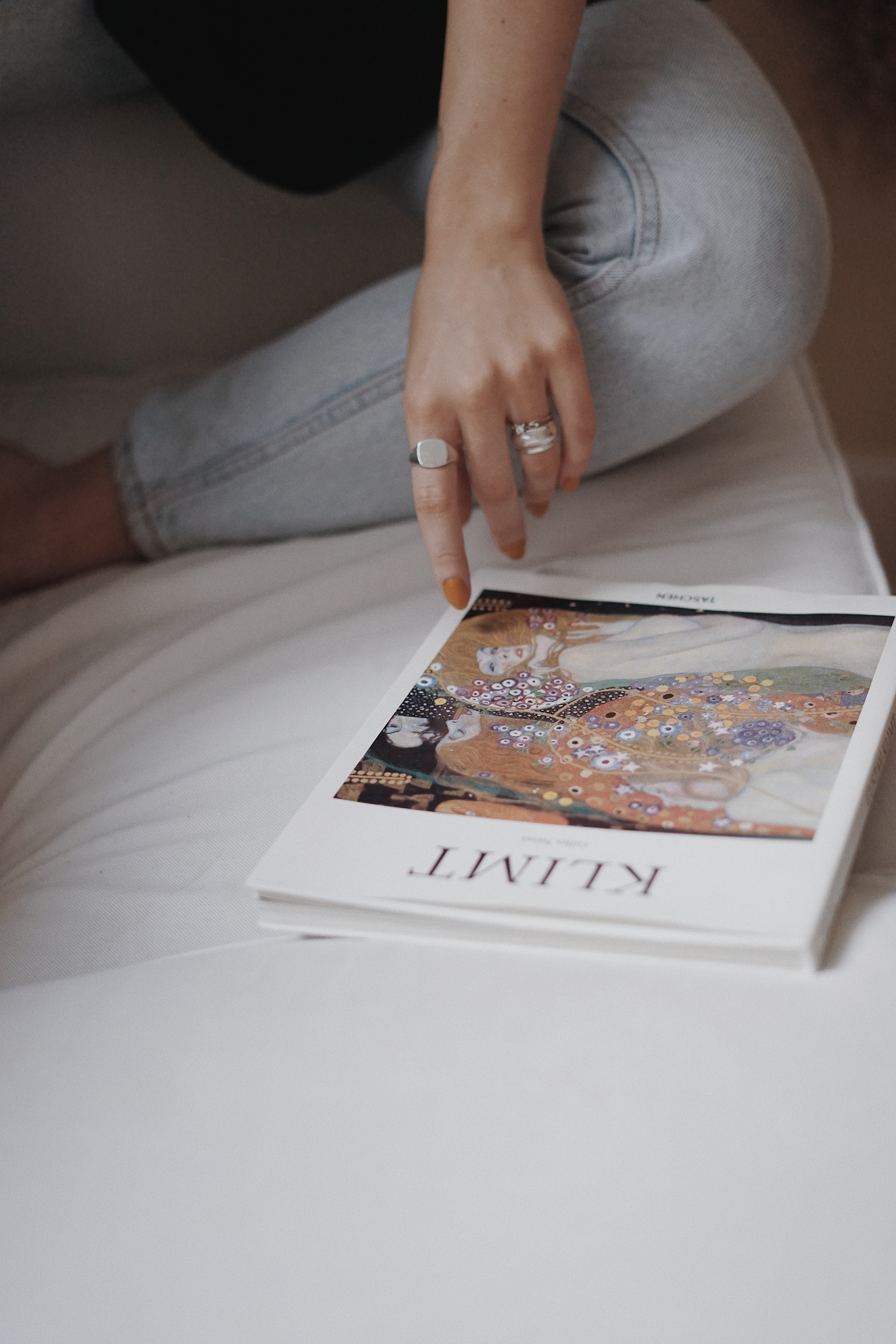 person-in-gray-denim-jeans-holding-white-and-brown-book