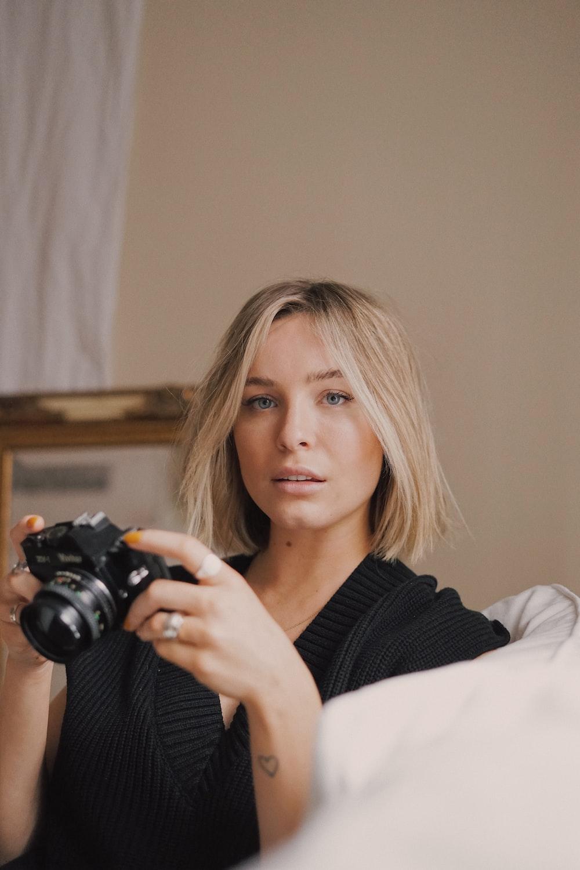 woman in black sweater holding black dslr camera