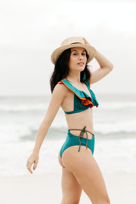 woman in blue bikini wearing brown straw hat standing on beach during daytime