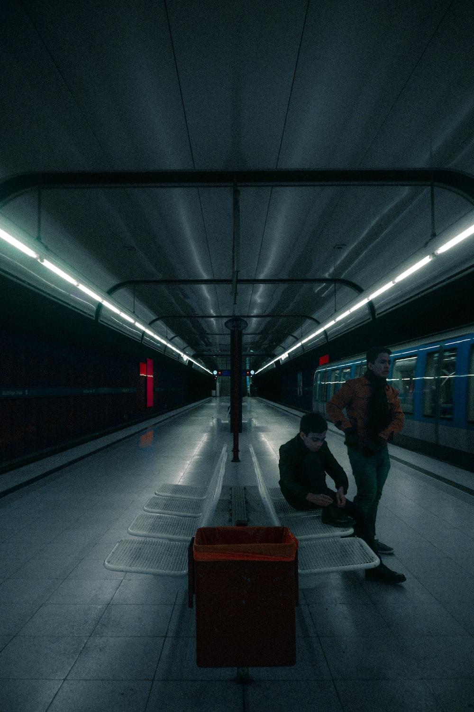 man in black jacket walking on train station