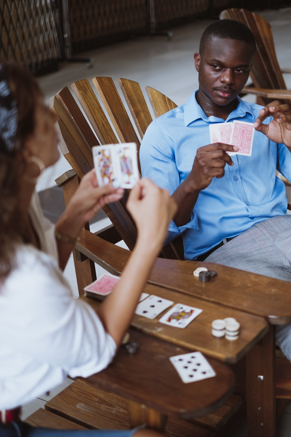 man in blue button up shirt holding playing cards
