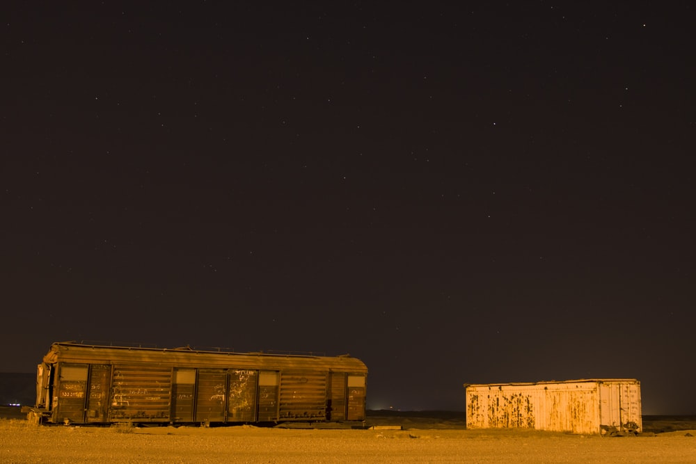 brown wooden house under black sky during night time