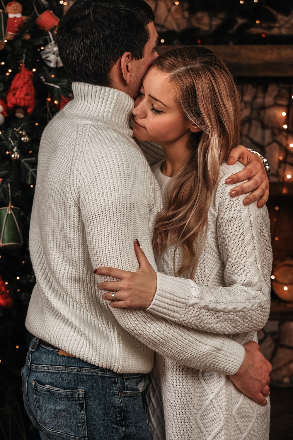 man in white sweater kissing woman in white sweater