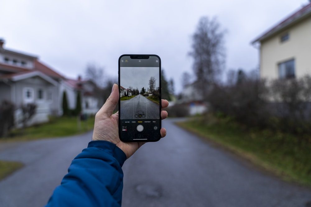 person holding black iphone 5 taking photo of road during daytime