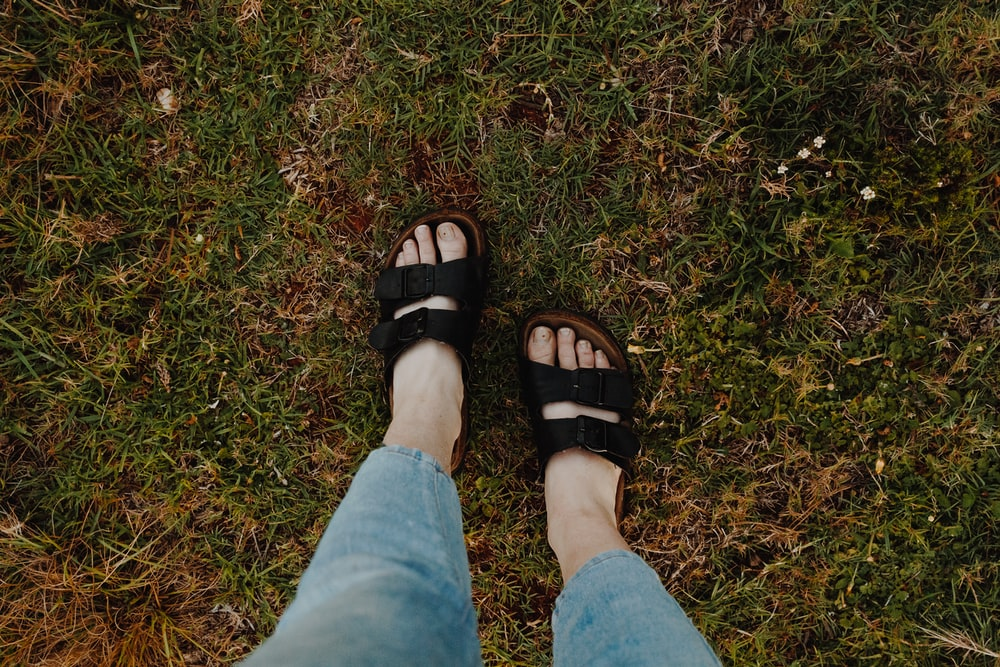 person in blue denim shorts wearing black leather sandals