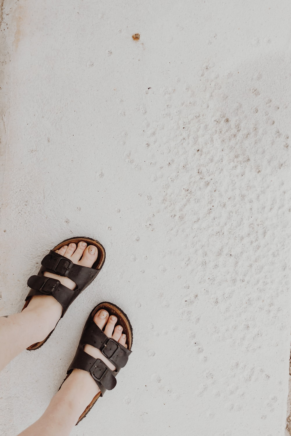 person wearing black leather sandals