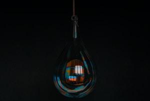 clear glass light bulb turned on in dim light