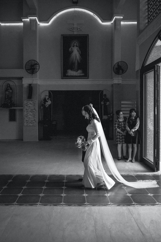 grayscale photo of bride and groom standing near door