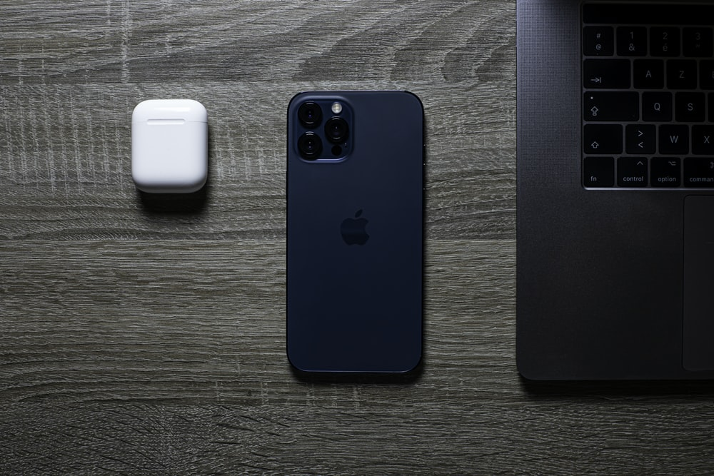 blue iphone 5 c beside white apple airpods charging case