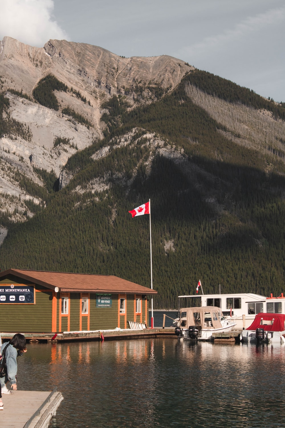 white and brown boat on dock near mountain during daytime