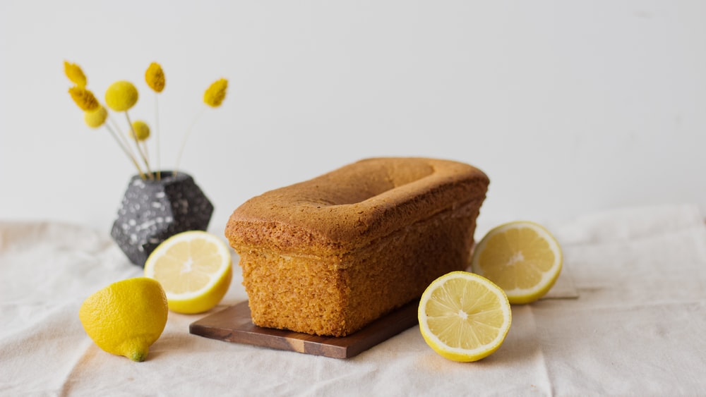 sliced lemon beside brown wooden container