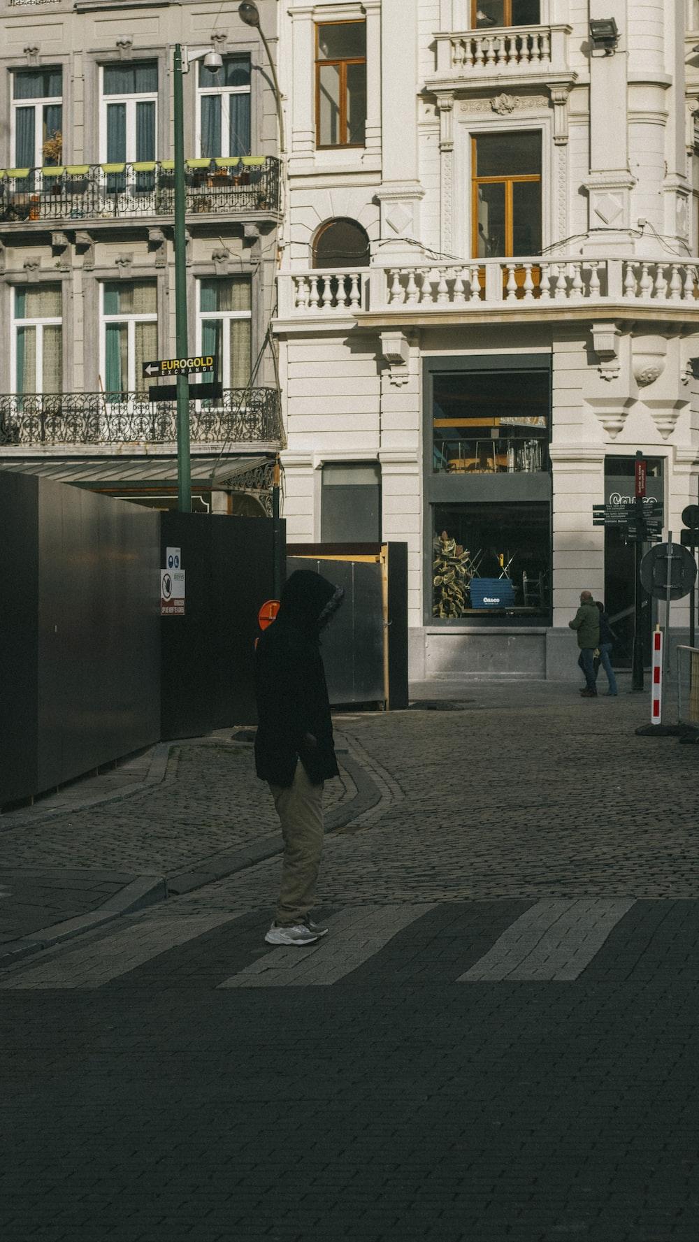 man in black jacket and gray pants walking on sidewalk during daytime