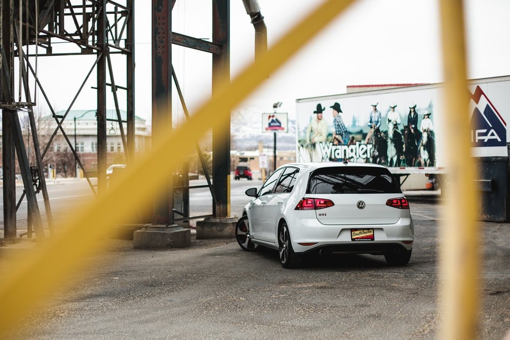white sedan parked near black metal fence during daytime