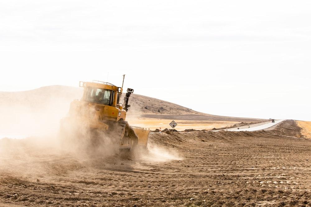yellow and black heavy equipment on desert during daytime