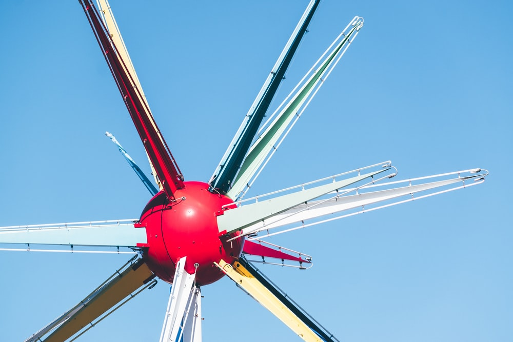 red and white wind mill under blue sky during daytime