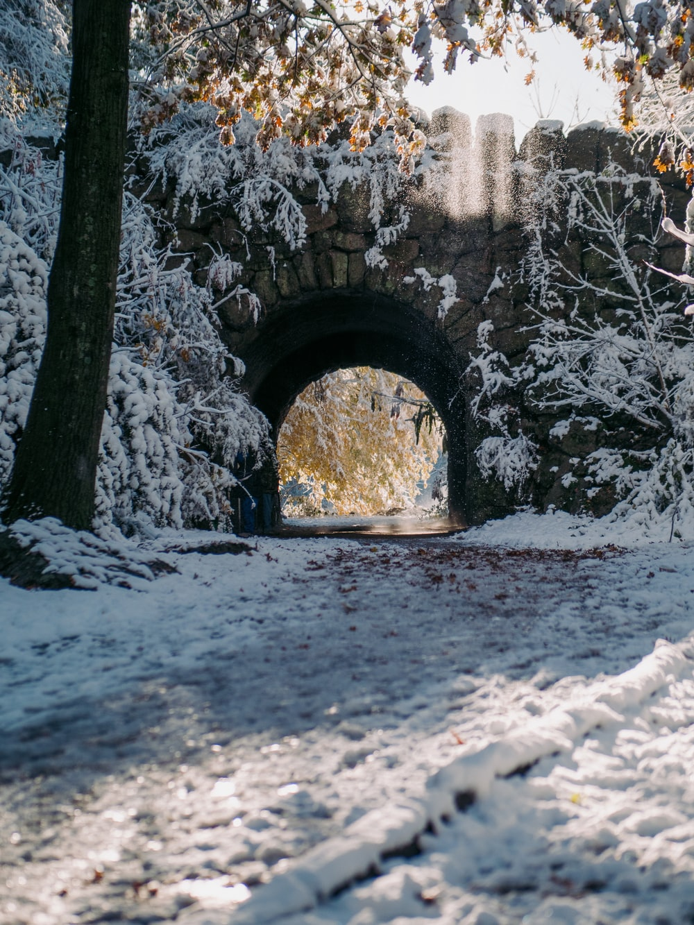 gray concrete arch with snow during daytime