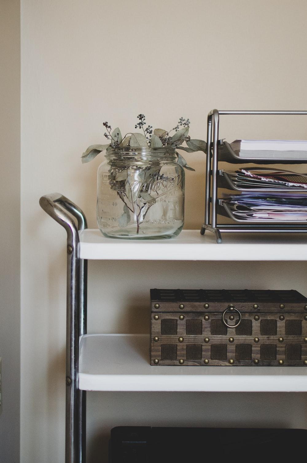 clear glass vase on white wooden shelf