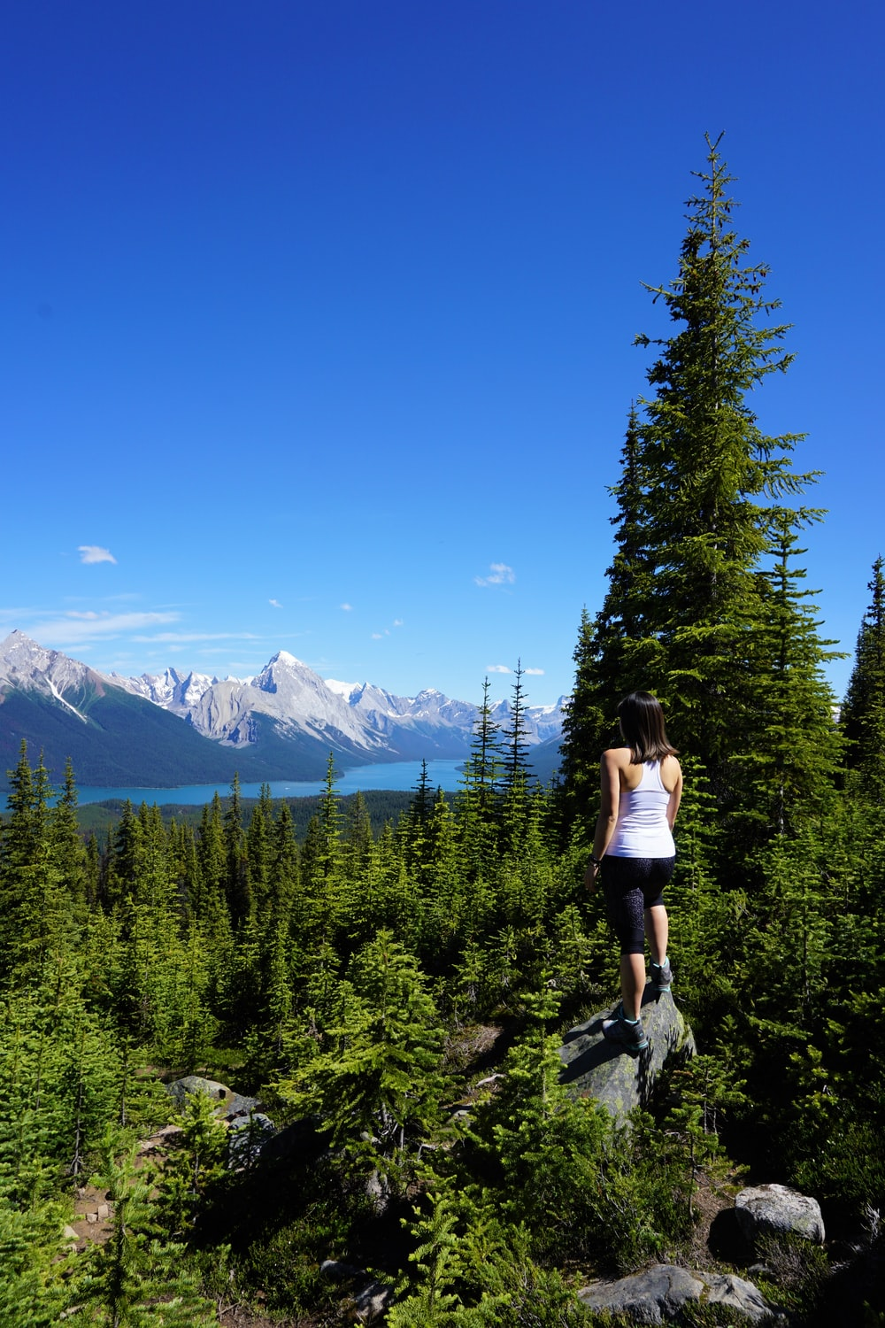 woman in black tank top and blue denim shorts standing on rocky mountain during daytime
