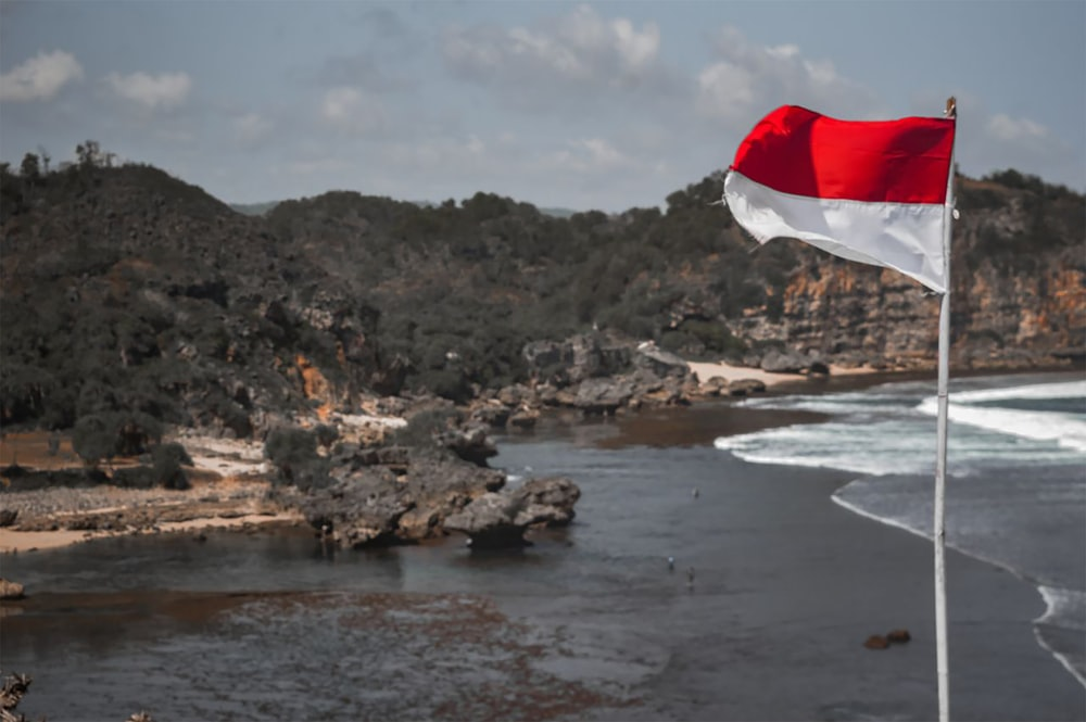 white and red flag on rocky shore during daytime