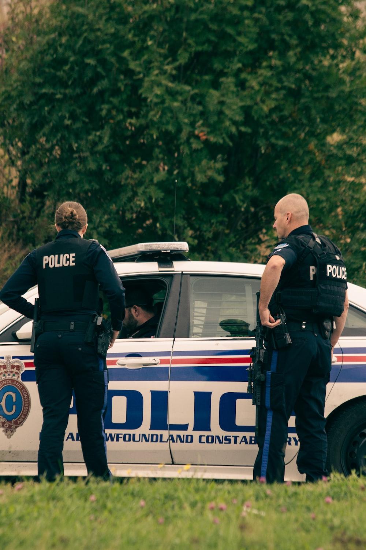 2 police men standing on white police car during daytime