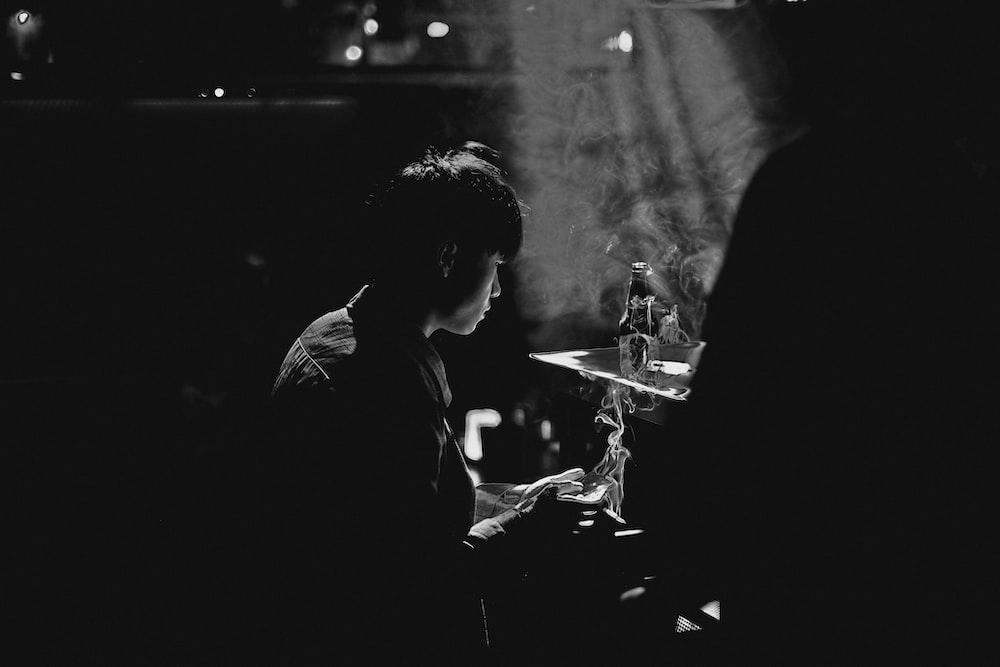 man in black jacket smoking cigarette