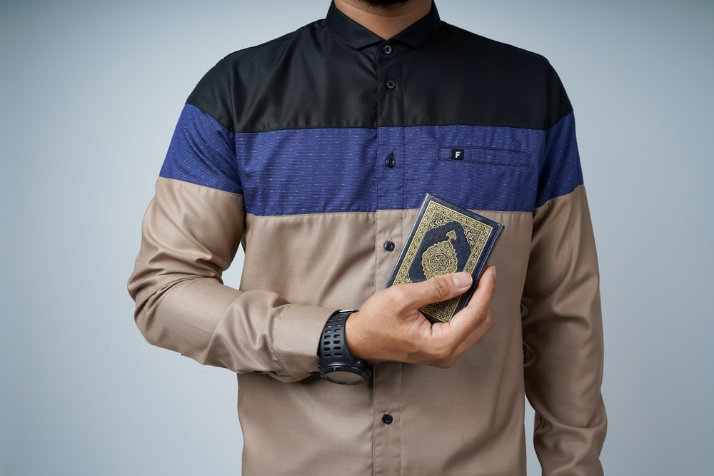 man in brown button up shirt holding 1 us dollar bill