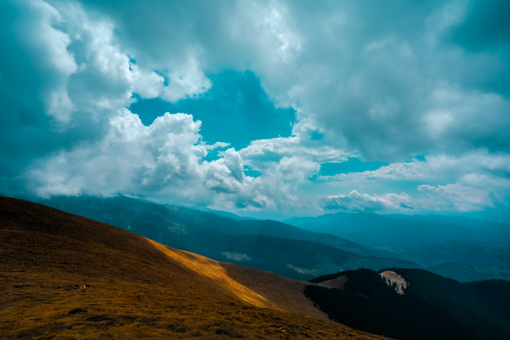 brown and green mountain under white clouds and blue sky during daytime