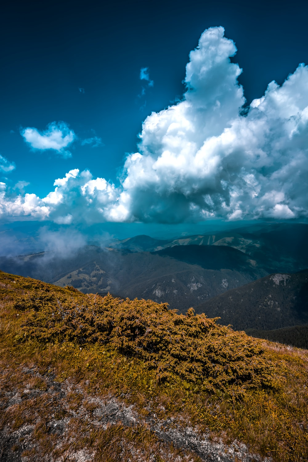 brown mountain under white clouds and blue sky during daytime