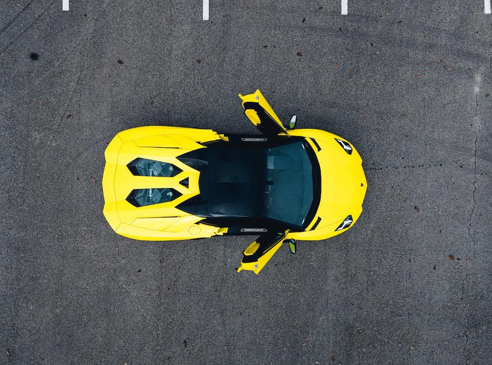 yellow and black sports car on gray asphalt road