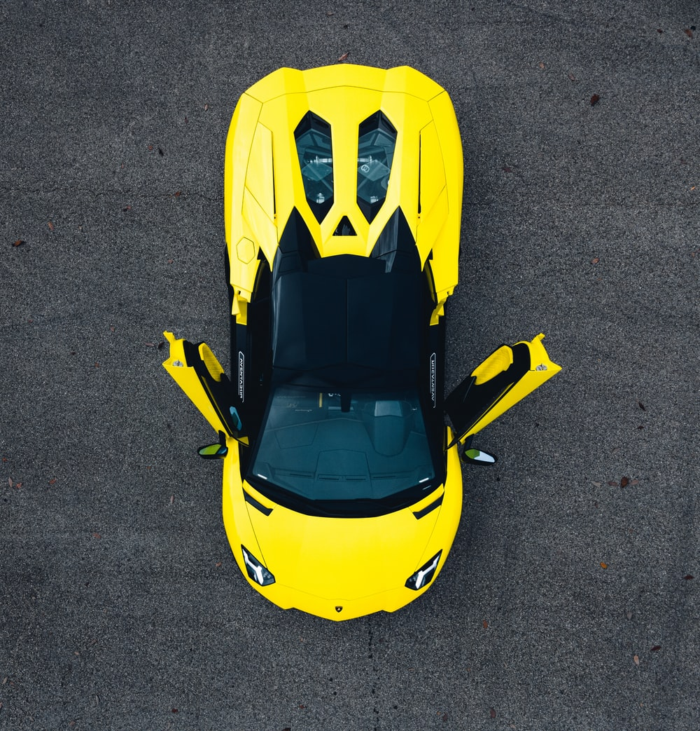 yellow and black car on gray asphalt road