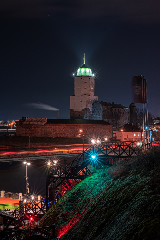 brown concrete building near bridge during night time