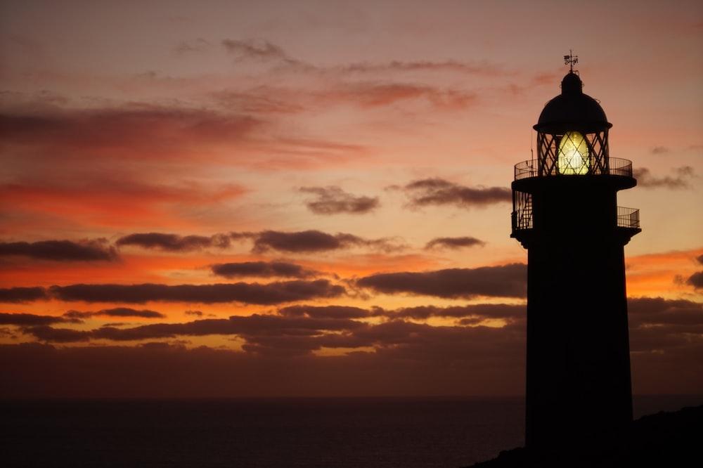 silueta del faro durante la puesta de sol