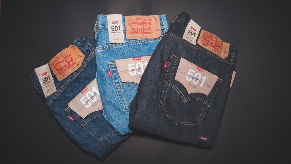 blue denim jeans on black textile