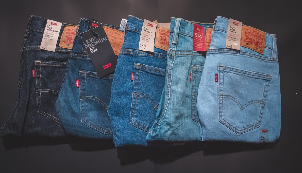 blue denim jeans on black surface