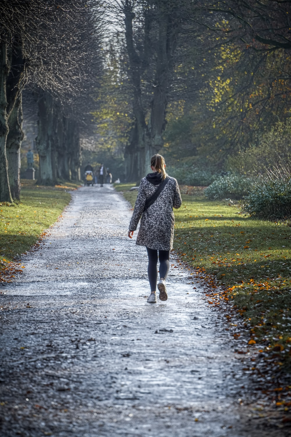 woman in black and white polka dot coat walking on pathway