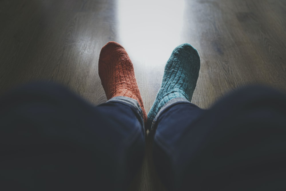 person wearing blue denim jeans and red socks