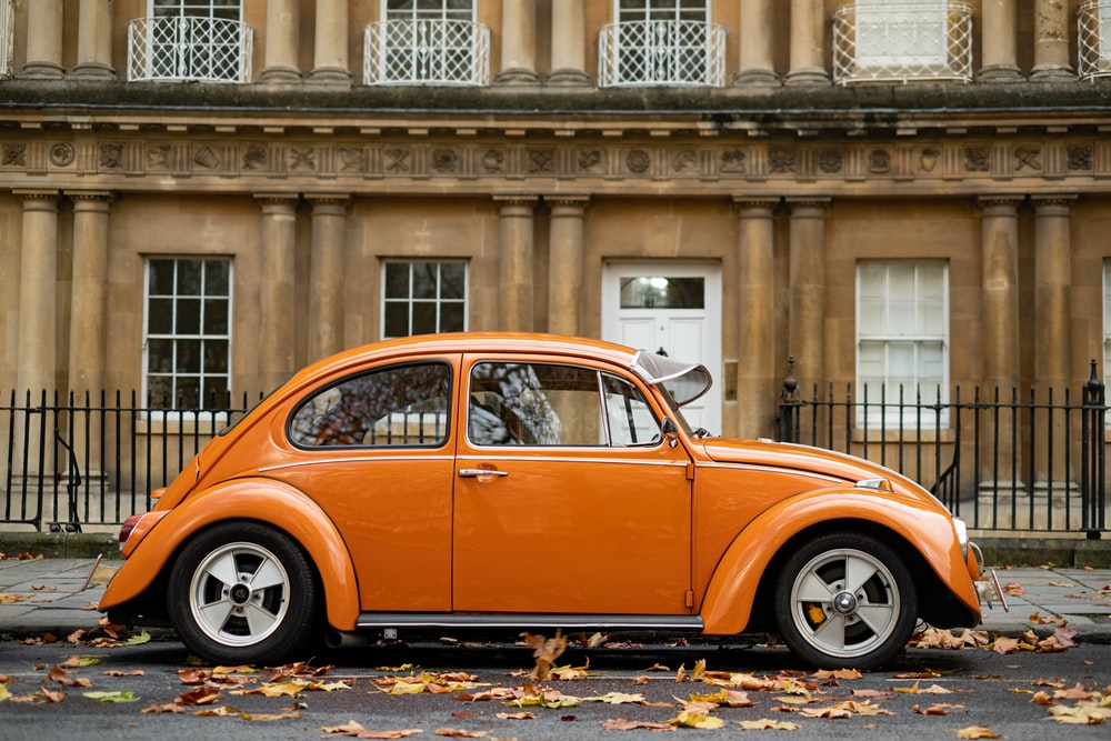 orange volkswagen beetle parked near building
