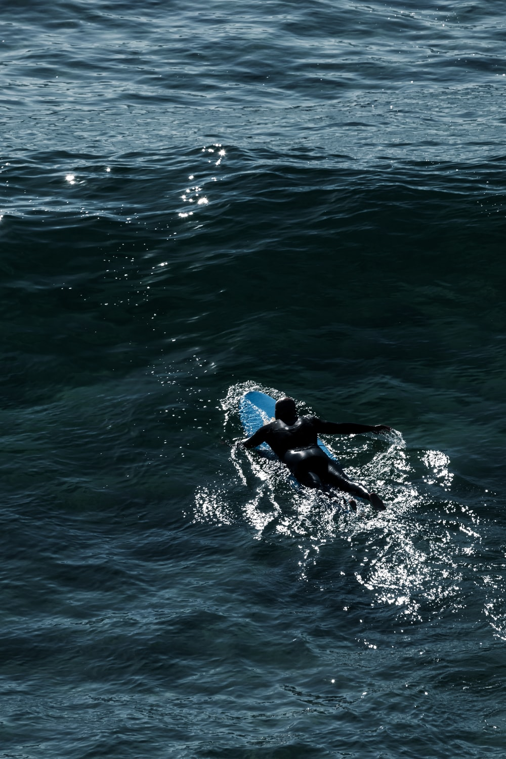 man in black wetsuit surfing on blue sea water during daytime
