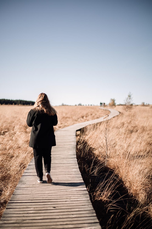 woman in black coat walking on brown wooden pathway during daytime