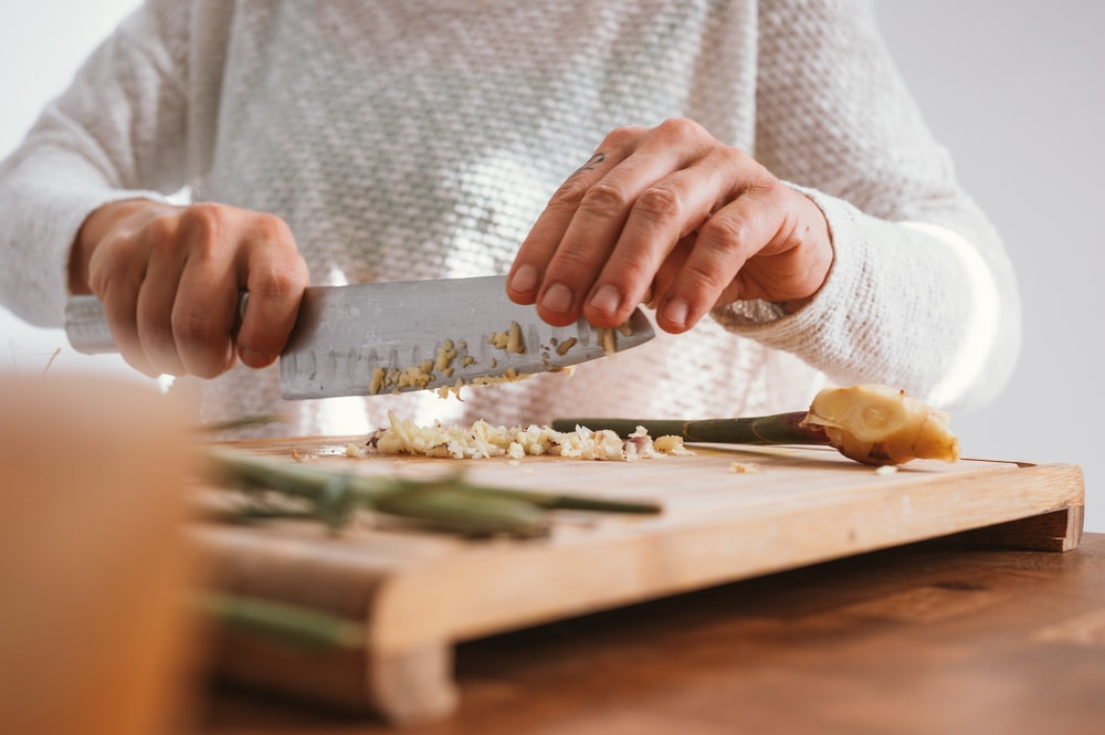 person holding knife slicing vegetable