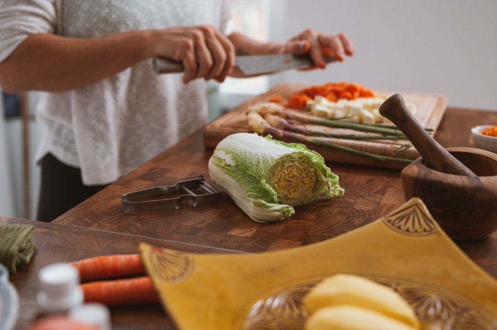 person slicing green vegetable on brown wooden chopping board
