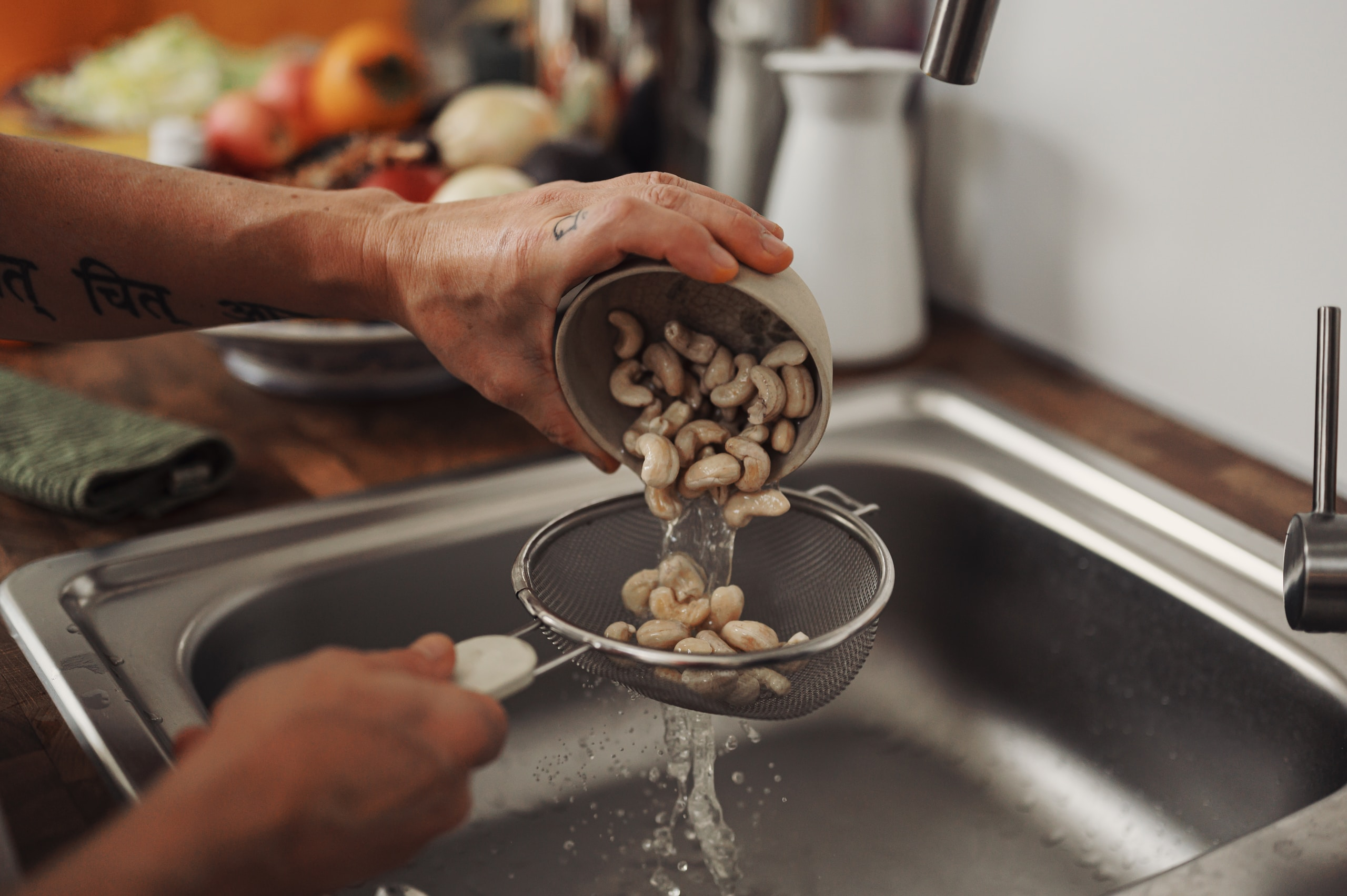 person holding stainless steel spoon with white and black beans