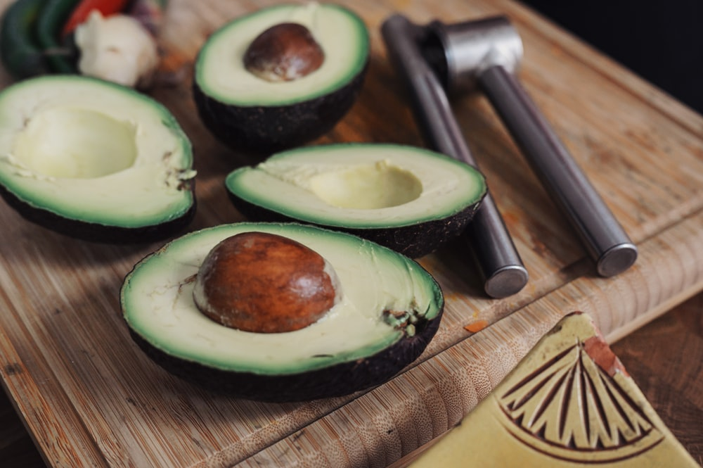 sliced avocado fruit on chopping board