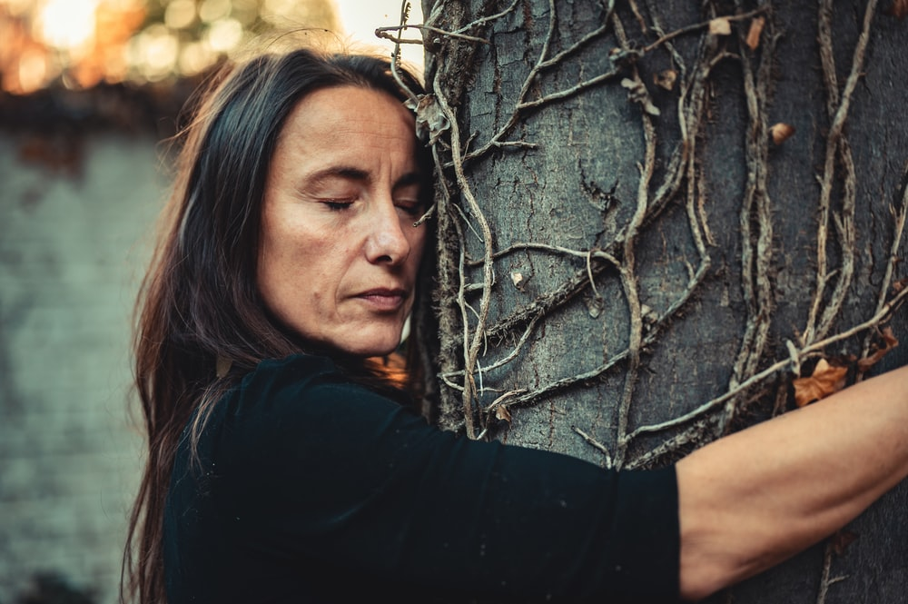 woman in black shirt leaning on brown tree