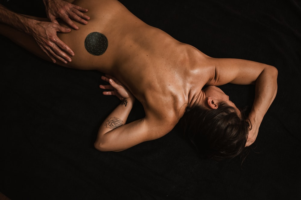topless woman lying on black textile