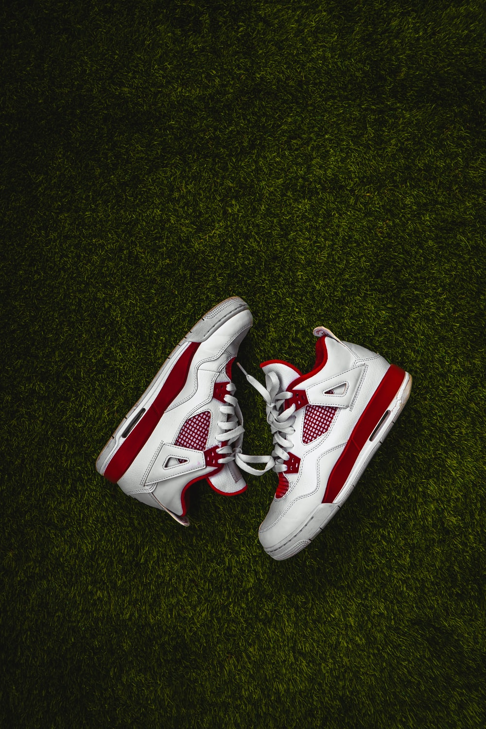 white and red nike basketball shoes on green grass
