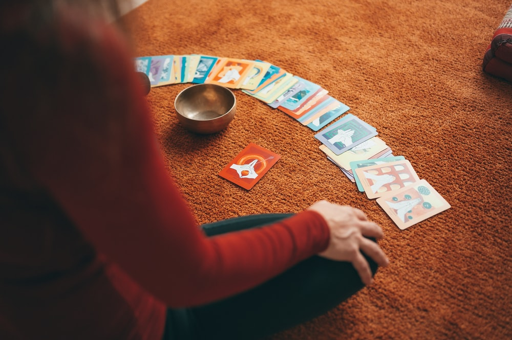 person in red long sleeve shirt holding playing cards