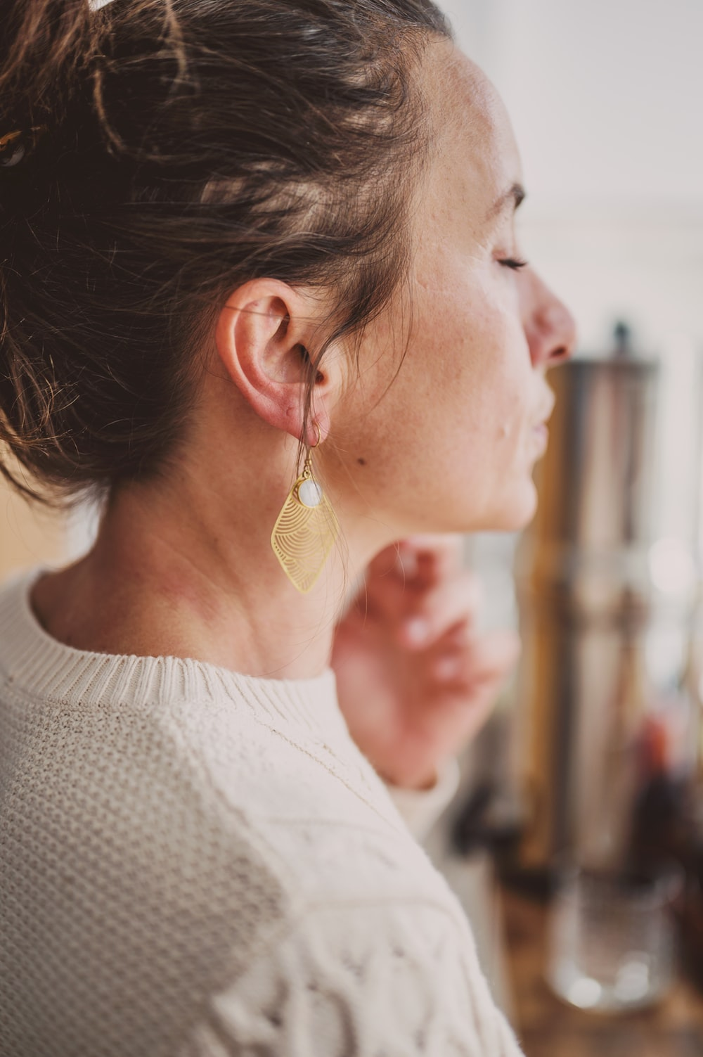 woman in white crew neck shirt wearing gold heart earring