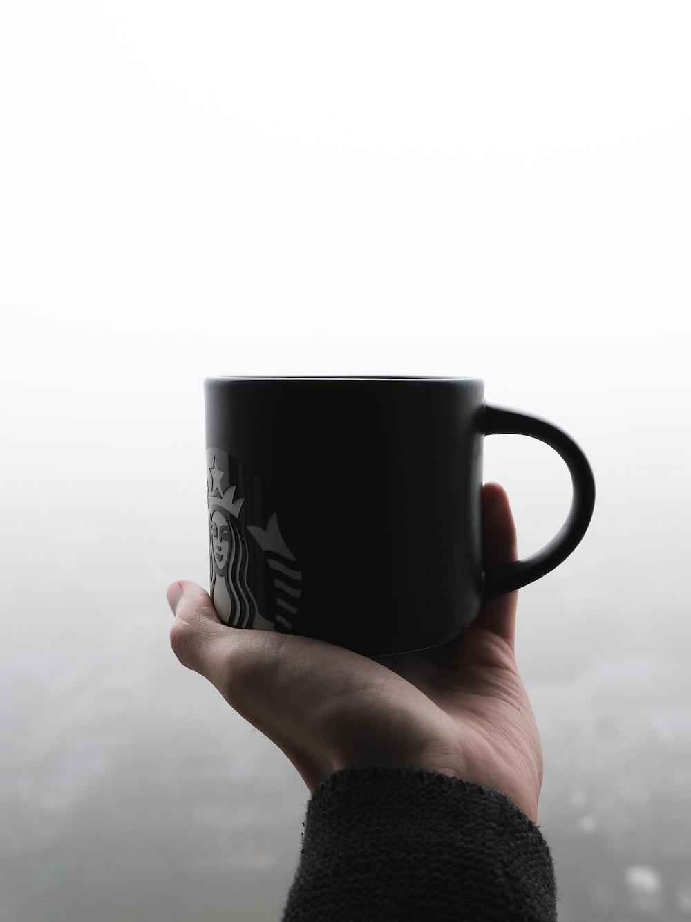 person holding black ceramic mug