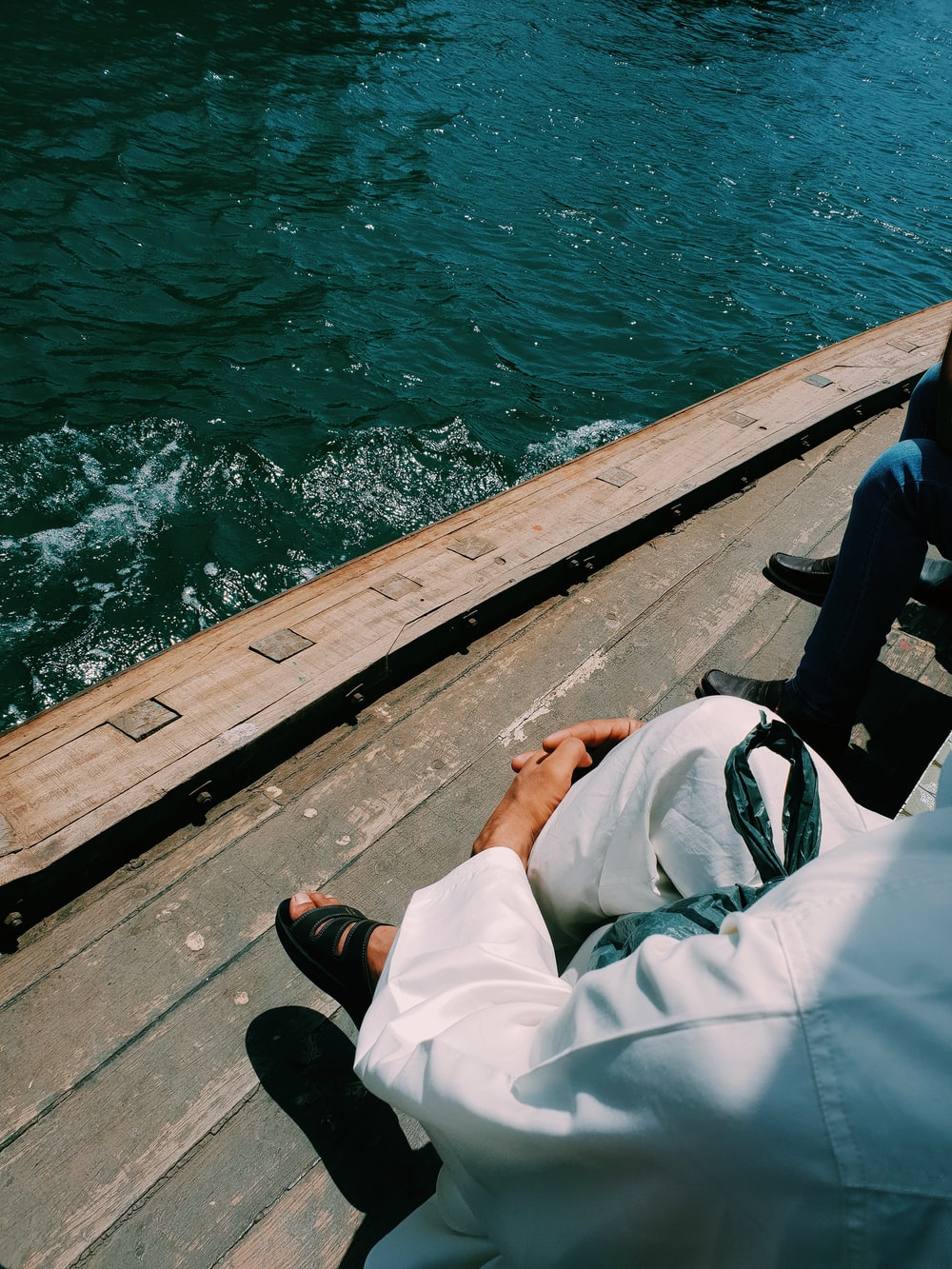 person in white shirt and black pants sitting on brown wooden dock